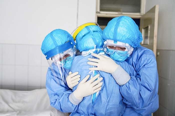 На этом снимке, сделанном 28 января 2020 года, показаны медицинские работники, которые обнимают друг друга в изоляторе в больнице в Цзупине в китайской провинции Шаньдун.