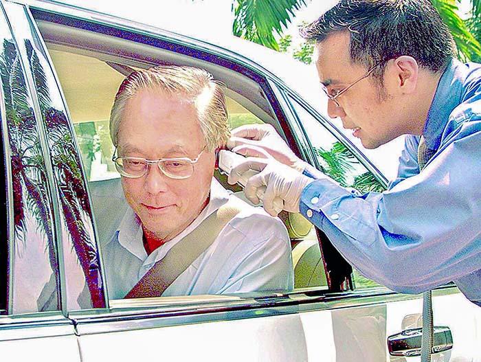 Премьер-министр Сингапура Го Чок Тонг получает свою температуру вне парламента 24 апреля 2003 года.